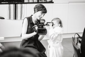 Female wedding videographer is crouched down with a smile to show a little flower girl how her Mummy the bride looks on her video camera as they get ready for a wedding near Manchester