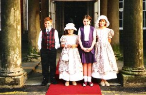 two young bridesmaids or flower girls standing in front of colwick hall with two other children wearing matching flowery dresses and hats from a late 80's or 90s wedding in Nottingham