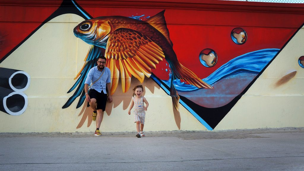 A little girl runs excitedly towards to camera as her Dad stands by a dramatic flying fish graffiti art on the streets of Lisbon