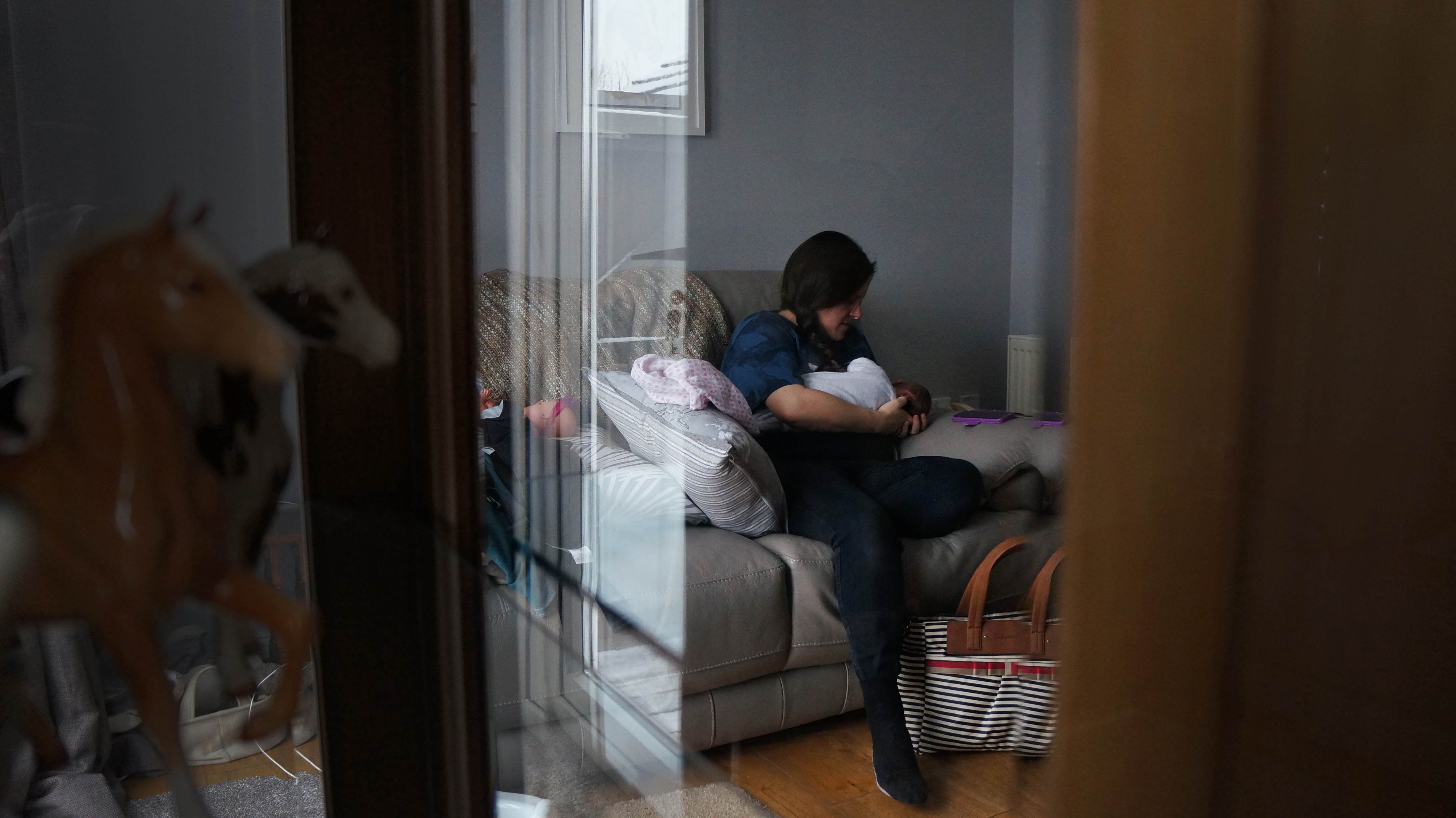 A mum sits on her grey leather sofa breastfeeding her newborn daughter