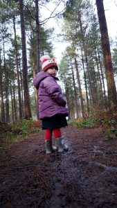 A young 2 year old girl all wrapped up for winter with a snowman hat on turns to spot the camera taking a photograph in staplefood woods