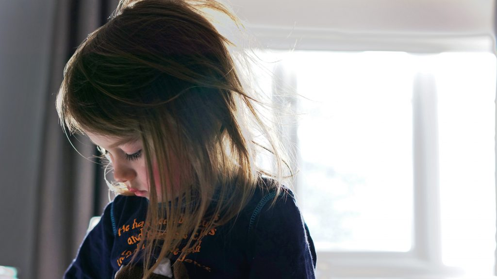 a photograph of a young girl sat in front of a bright window looking down with her hair all messy from a good nights sleep