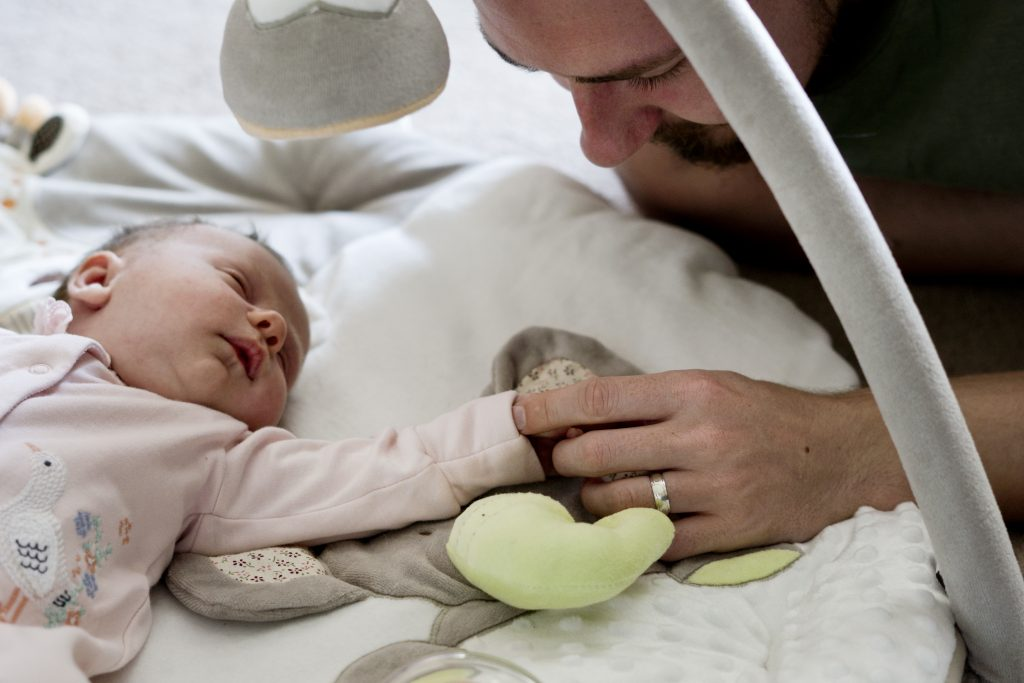 daddy and newborn daughter hold hands as she lays on her neutral coloured play mat in their living room in Lancashire for their family photographer