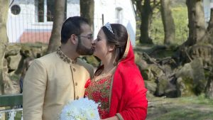 the bride and groom share a kiss in the dappled sunlight at southports botanic gardens. she wears a bangladeshi wedding saree in bright red and holds a simple white bridal bouquet