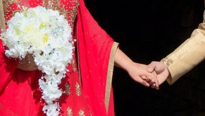 the bangladeshi wedding saree in red looks vibrant in the bright sunshine for the wedding video. The bride and groom are holding hands