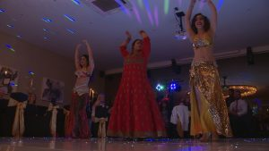 a bride in a traditional red bangladeshi wedding saree dances inbetween 2 belly dancer friends to entertain their wedding guests at the bold hotel