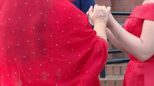 a close up of the brides banglideshi dress with gold details and her heart shaped brown henna on her hand as she holds her sister and bridesmaids hands outside church