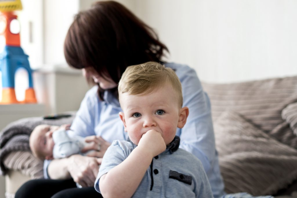 a little boy chews his hand as he looks at the camera His mum is holding her newborn son on the sofa behind him