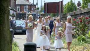 the bride and her bridal party walk down the stone path to make their way in to st johns church in Burscough for the wedding ceremony the bridesmaids are wearing full length lilac purple dresses and holding cream flowes