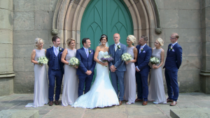 the bridal party pose with the bride and groom in lilac and navy