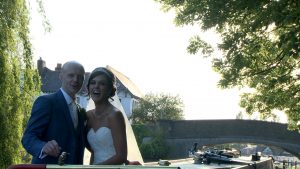 the bride laughs at the wedding videographer as they finish posing on the canal boat by burscough wharf
