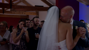 the groom gives his bride a kiss on the neck during a romantic first dance to ed sheeran at the blue mallard in lancashire for their wedding video by love gets sweeter