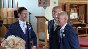 The groom waits by the alter in St Johns church in burscough looking nervous with his best man and dad