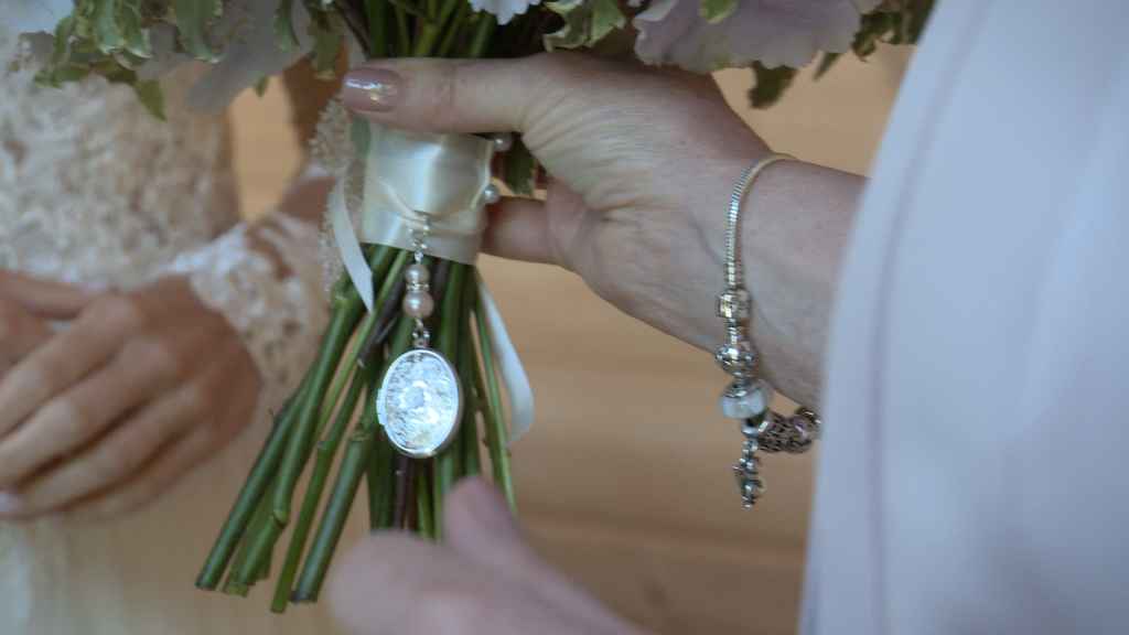 A close up from the wedding video of a memory locket tied to the bridal bouquet ribbon