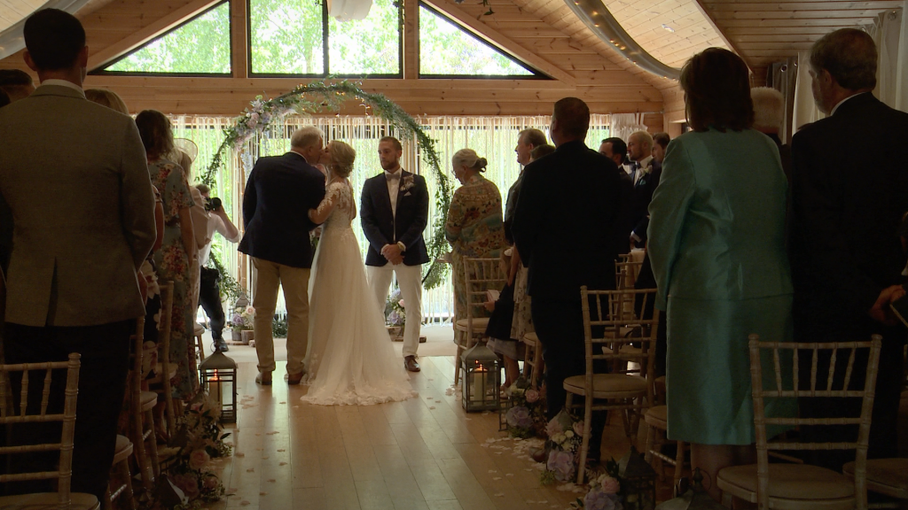 the bride kisses her dad on the cheek. A rustic large floral hoop in the background at their Styal Lodge wedding