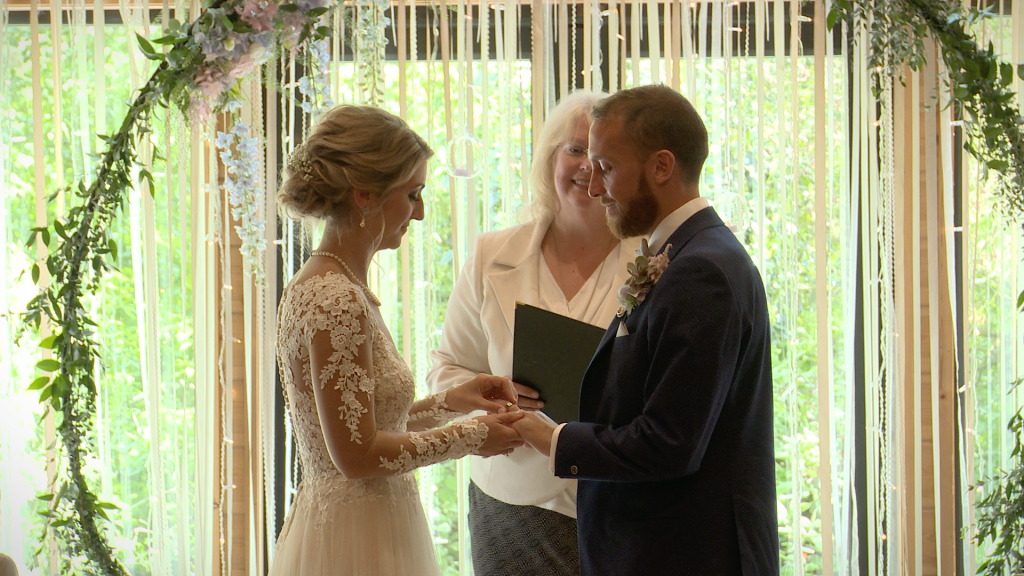 the bride and groom exchange wedding rings during their ceremony Styal Lodge in Cheshire