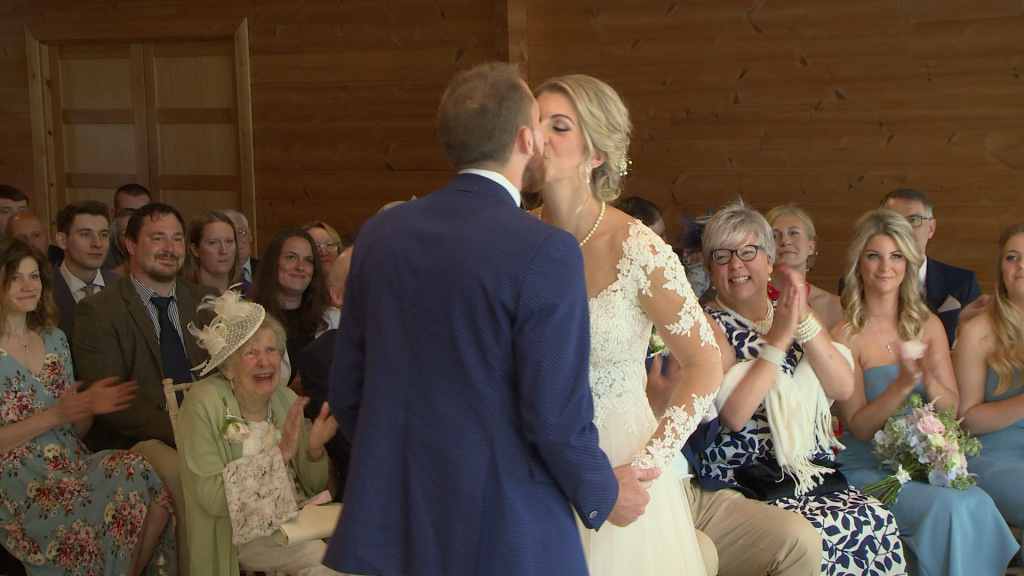 A video of you may kiss the bride and the guests are smiling and clapping behind them at Styal Lodge in Cheshire
