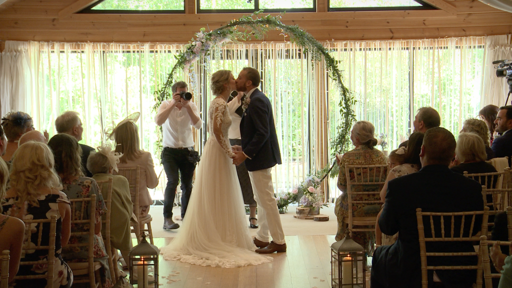A still from the wedding video of a rustic Styal Lodge wedding with large floral hoop and aisle of white petals
