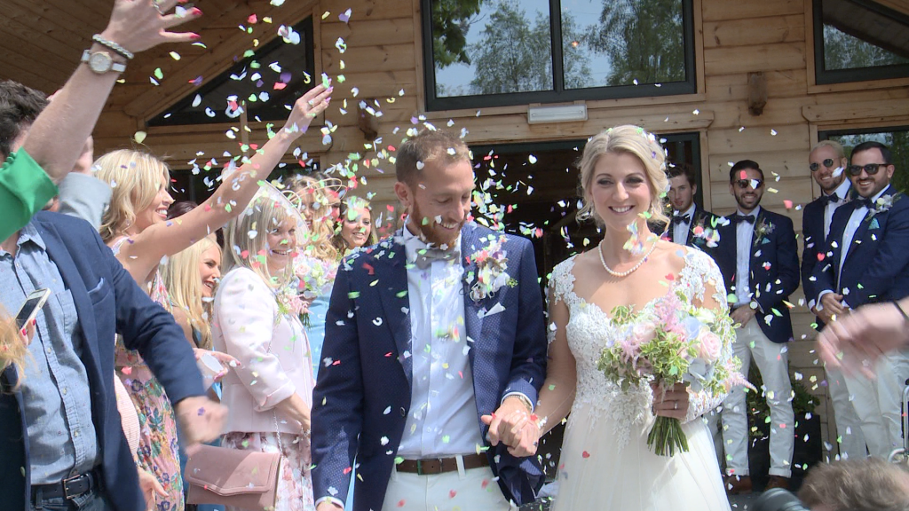 the bride and groom are showered in bright coloured natural petal confetti outside Styal Lodge in Cheshire for their wedding video