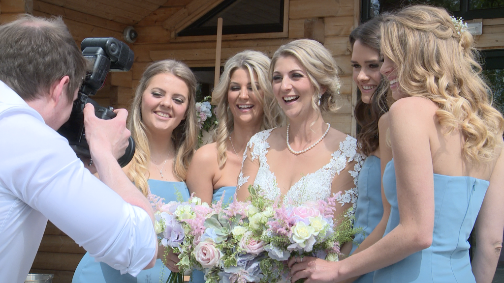 the bridesmaids have a giggle with the wedding photographer Daniel Lloyd outside Styal Lodge in Cheshire