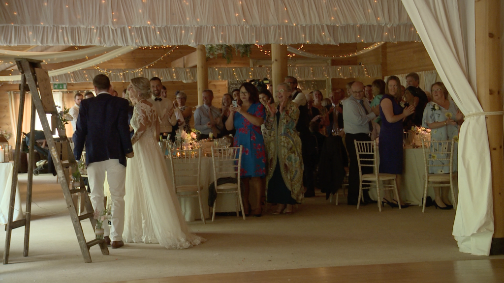 the bride and groom dance through the tables during their entrance for the wedding reception at Styal Lodge in Cheshire caught on the wedding video