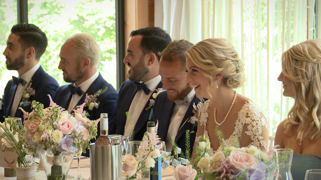 the bridal party laugh on their vintage inspired top table as the father of the bride delivers his speech at Styal Lodge