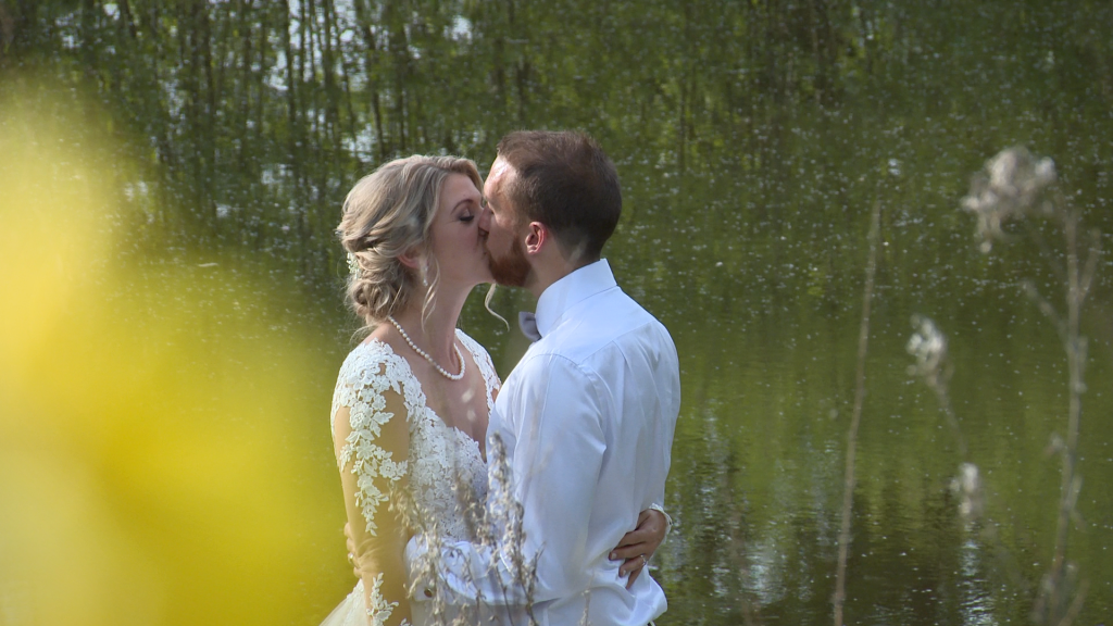 a wedding video still of a bride and groom have a kiss on the jetty in front of the lake at Styal Lodge in Cheshire