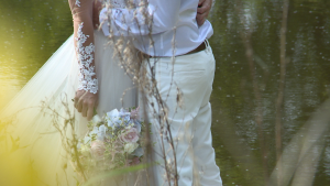 a close up shot of the brides lace sleeve of her wedding dress and pretty pink, white and blue bouquet at Styal Lodge in Cheshire