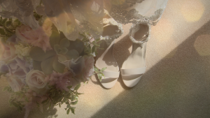 a stunning hand tied garden flower style bridal bouquet sits next to a pair of bridal sandals