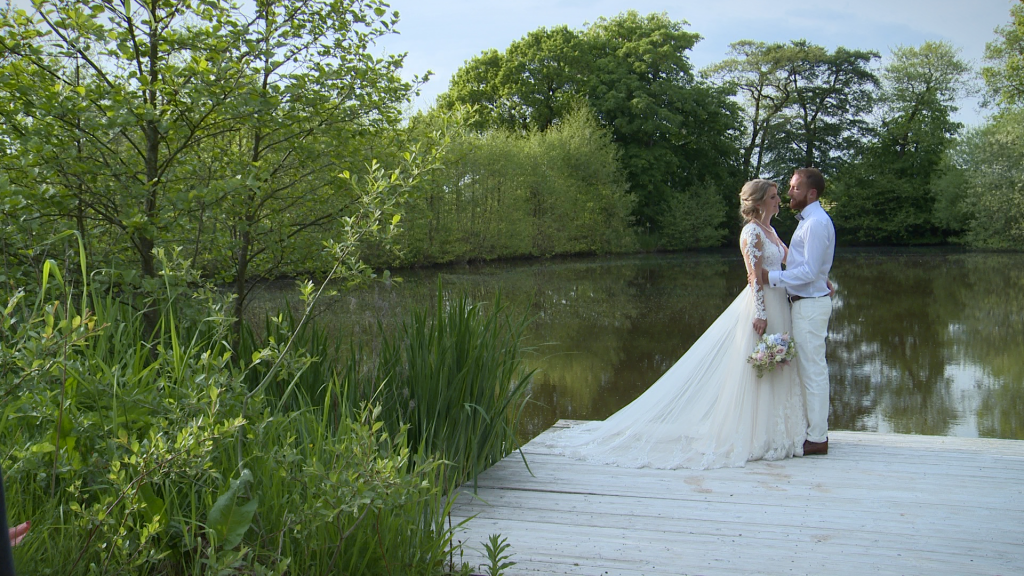 a wider shot of the bride and groom having a chat by the lake Styal Lodge in Cheshire taken from their wedding video