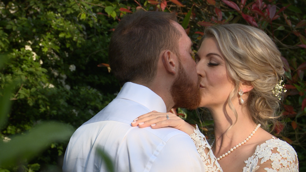 Bride and groom kiss posing for their wedding photographer and videographer at Styal Lodge in Cheshire