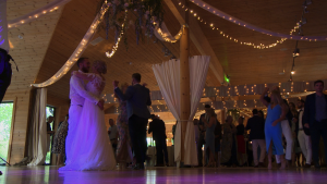 the bride and groom are joined on the dancefloor for their first dance under a floral hoop and festoon lights at Styal Lodge in Cheshire