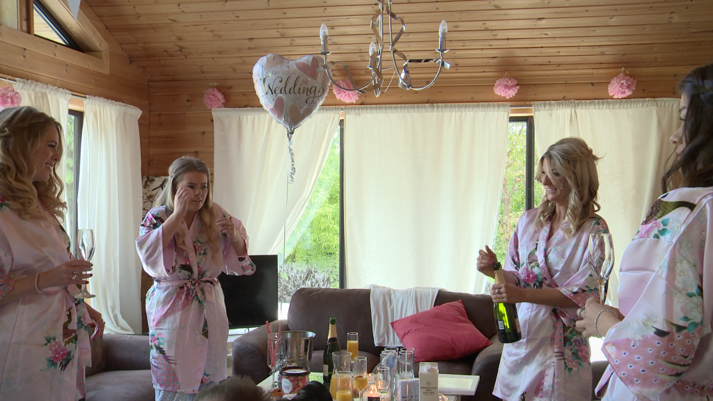 bridesmaids react to the champagne popping to celebrate a Styal Lodge wedding