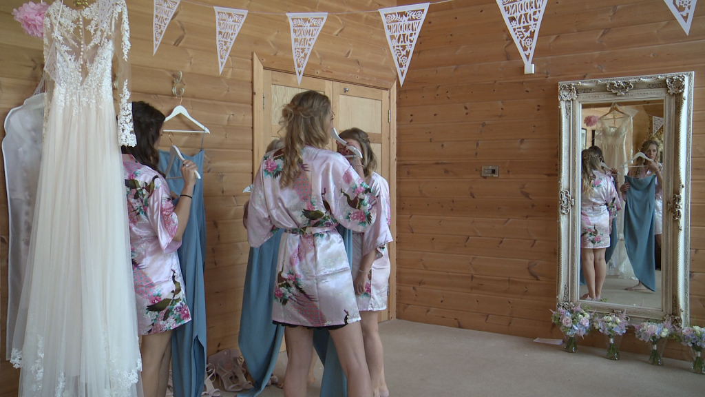 Bridesmaids stand in their silk floral dressing gowns as they pick their blue bridesmaid dresses at styal lodge