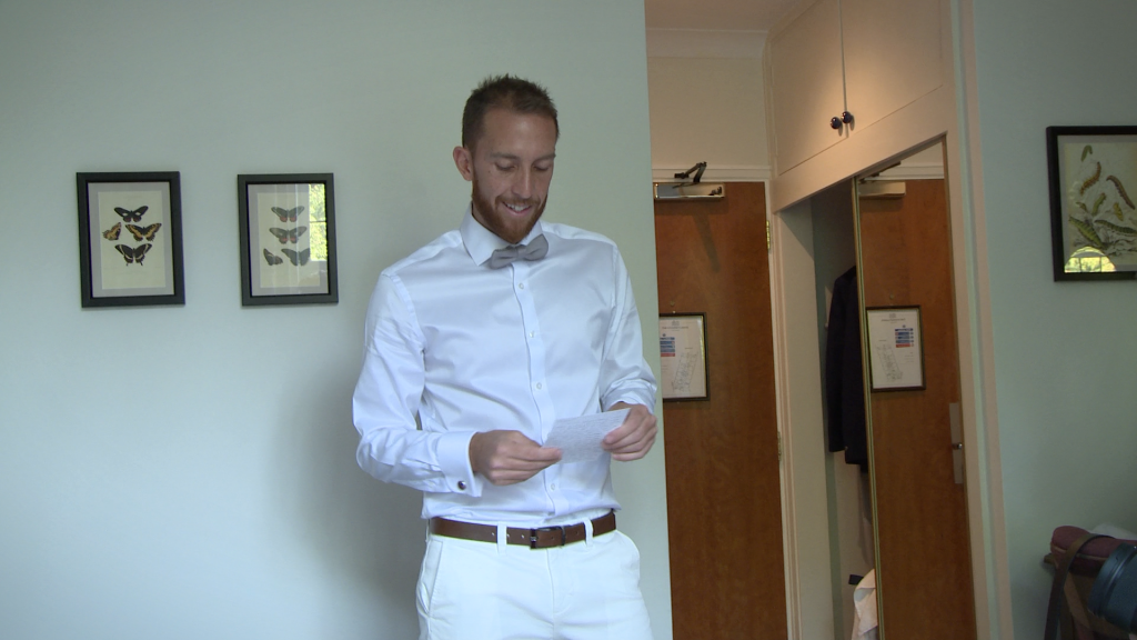 the groom smiles as he reads the wedding card sent by his bride to be waiting at Styal Lodge