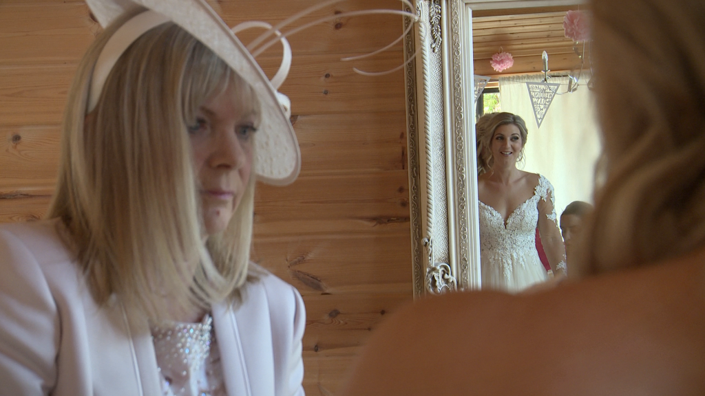 mother of the bride checks her daughter in her wedding dress as she smiles at herself in the mirror in styal lodges bridal room