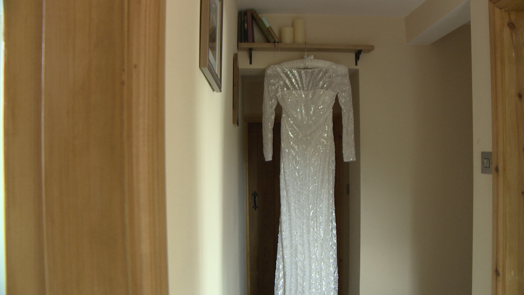 A long floor length beaded Eliza Jane Howell Gown hangs from a small bookshelf by a door on a cream silk bridal hanger