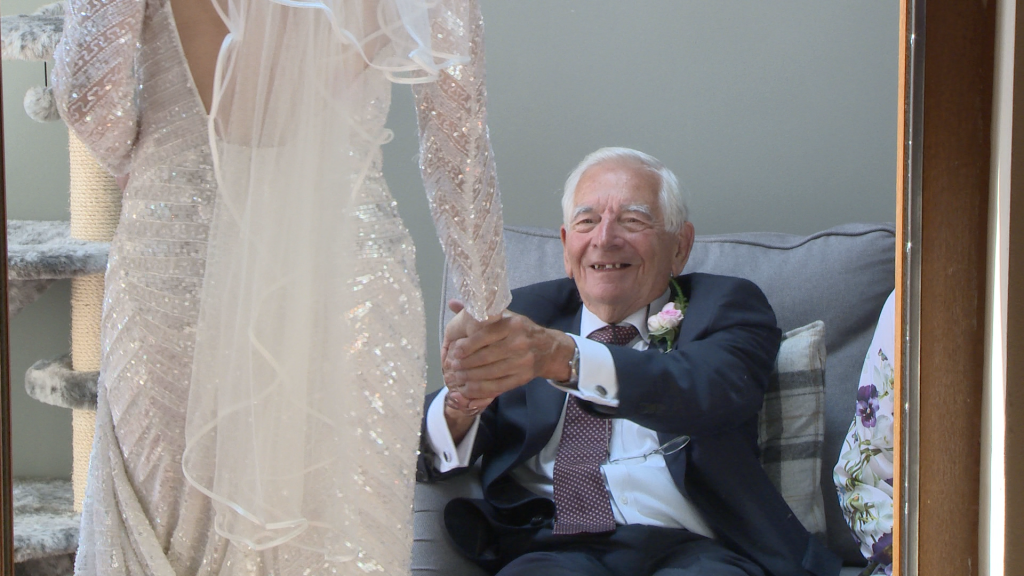 wedding videographer catches an emotional moment as grandad holds his grand daughters hand tightly with pride on her wedding morning in Liverpool as he sees her in her vintage inspired beaded wedding dress and veil for the first time