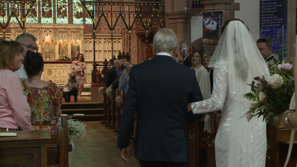a grandad walks his granddaughter the bride down the aisle at St Peters church in woolton