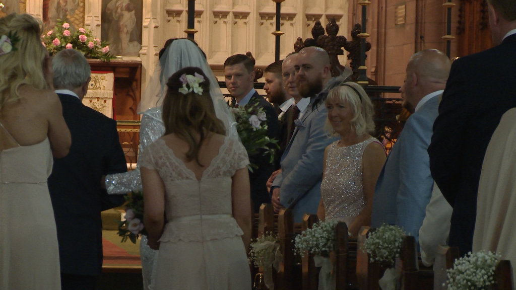the videographer at the back of St Peters Church in Woolton films the groom turning to see his bride walk towards him
