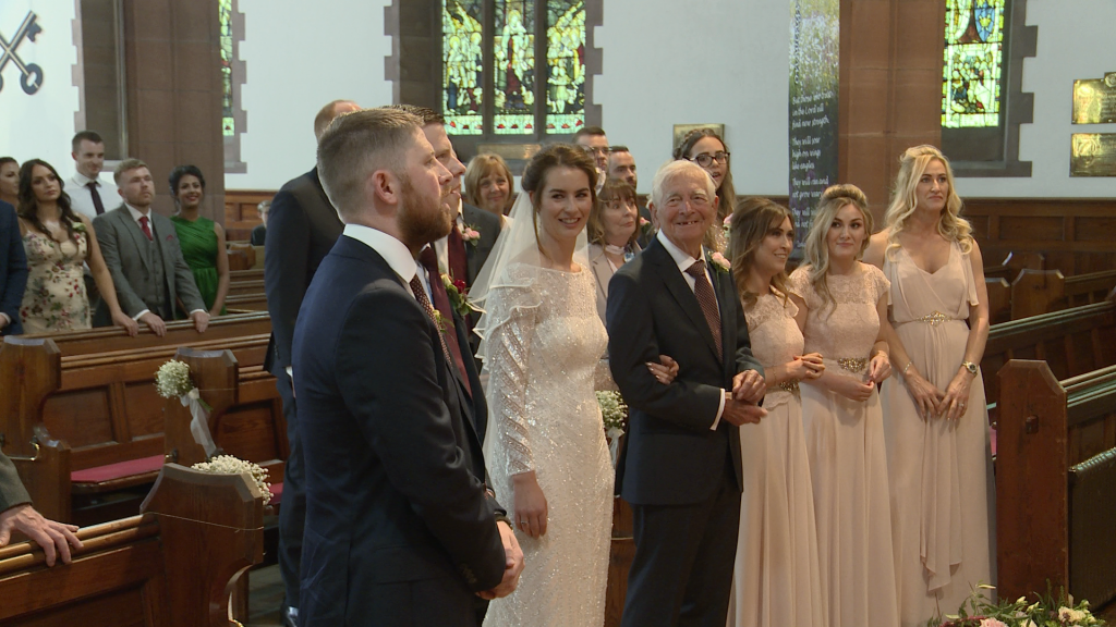 the bridal party smile as they stand at the top of the aisle at St Peters church