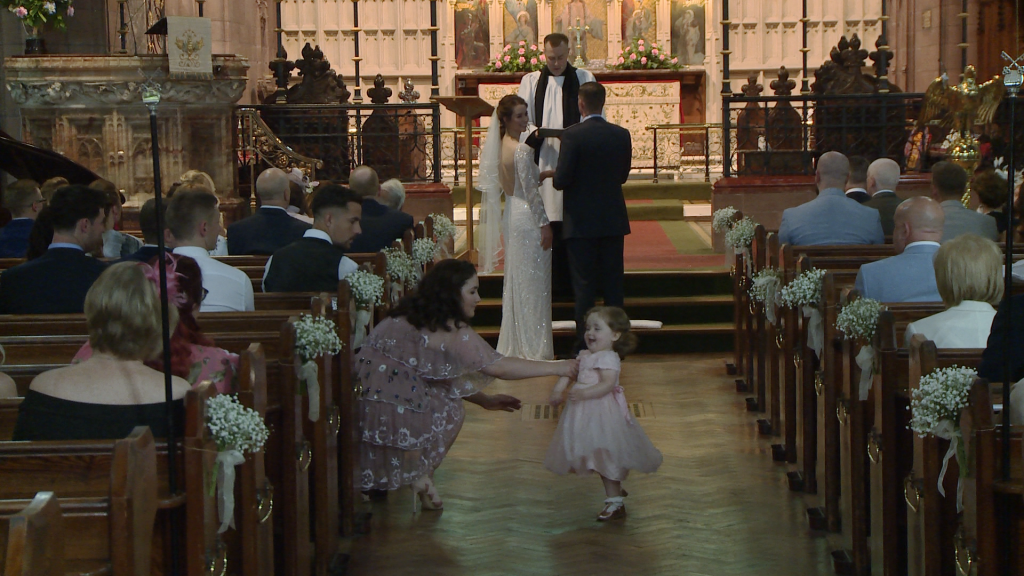 the videographer films a flower girl running down the aisle as her mum tried to catch her during a wedding ceremony at St Peters in Woolton