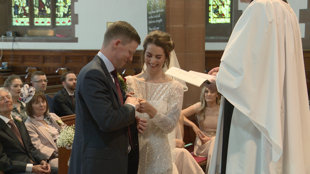 the bride and groom laugh as they try to fit the wedding rings on in front of the wedding video at their church ceremony in liverpool