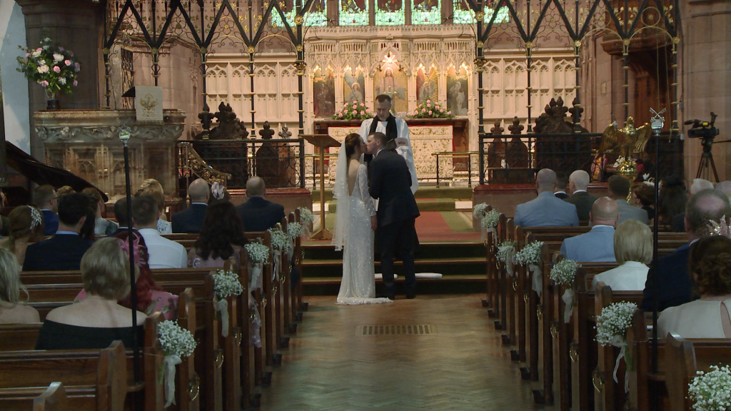 The bride and groom kiss as the priest announces you may kiss the bride in front of family, friends and the wedding videographer at St Peter's Church in Woolton Liverpool