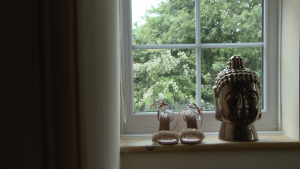 a pair of blush pink beaded bridal shoes sit on a window sill next to a bronzed Buddha head