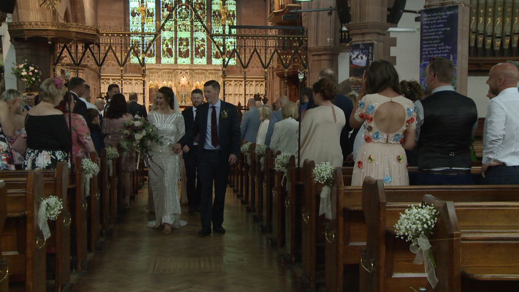 the bride and groom walk back down the aisle as husband and wife at St Peters in Woolton village