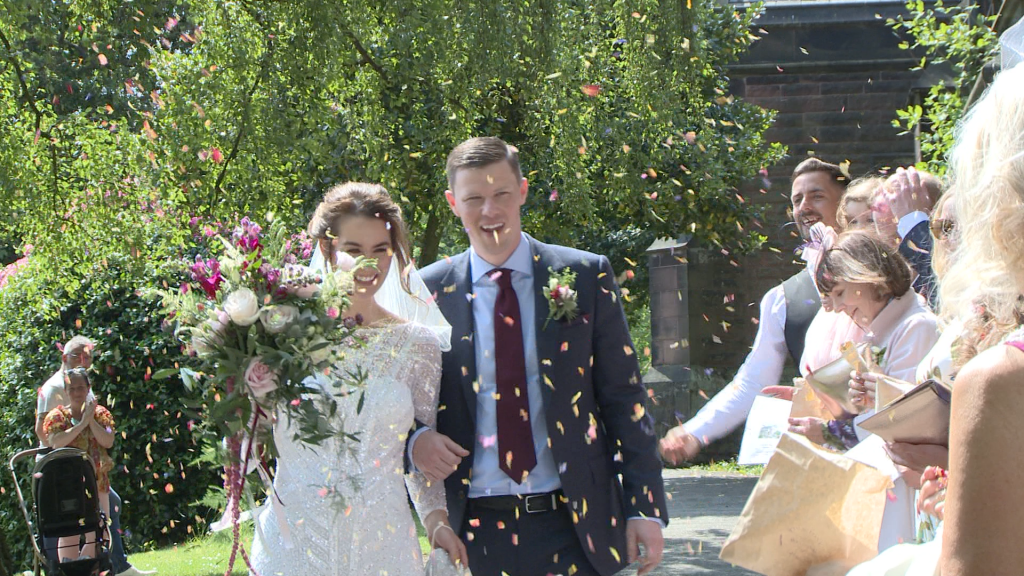 confetti is thrown at the bride and groom as they make their way through the lychgate at st peters in woolton