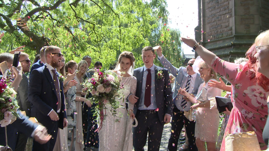 an Eliza Jane Howell bride holds a pink and purple rustic hand tied oversized bouquet holding her dress and linking her grooms arm as they get showered in confetti outside St Peter's Church for their Liverpool wedding