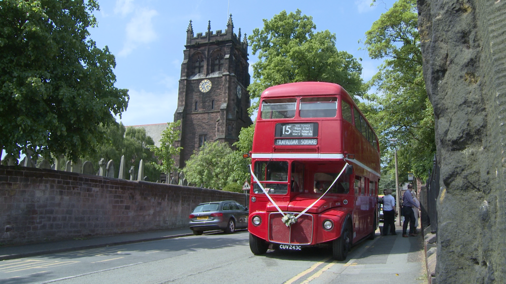 a vintage red double decker london bus with white wedding ribbon on is parked outside St Peters church in woolton on a summers day