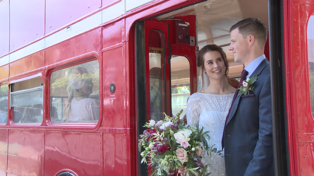 the bride wearing a beaded Eliza Jane Howell dress and holding a rustic purple and pink bouquet and groom wearing a blue grey informal suit and purple tie chat standing on the back of the red london bus after their wedding ceremony at St Peters Church in Woolton Liverpool